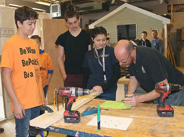 [PIC] Student Participant and CTI Judge Look Over Wood Working Excercise
